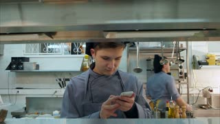 Head chef asking young trainee not to use phone in the kitchen
