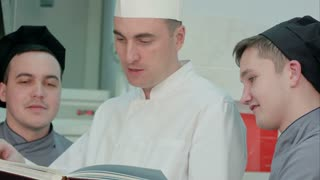 Head chef holding recipe book and discussing something with his trainees