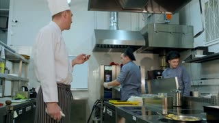 Head chef reading online orders from his phone and giving tasks to cooks