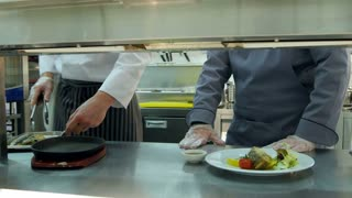 Head chef showing his assistant how to serve fish on an iron platter