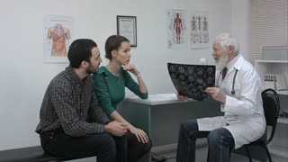 Healthcare and medical concept. Doctor with patients looking at x-ray.