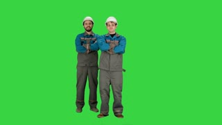 Industry, building, construction and people concept - happy male builders on a Green Screen, Chroma Key