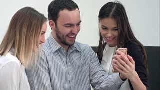 Laughing male worker and two female coworkers taking selfies in the office