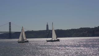 LISBON, PORTUGAL - september, 2015: 2 yachts at the tejo river, background - The 25 de Abril Bridge over Tagus River Yacht