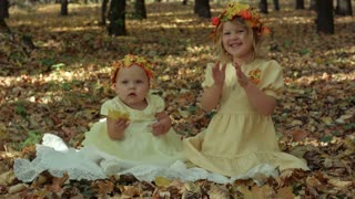 Little baby and girl in the autumn park
