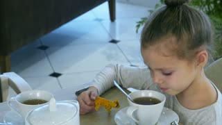 Little blond girl drinking tea from spoon while her parents are busy with tablet