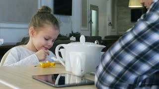 Little blond girl drinking tea sitting in cafe with her lovely parents