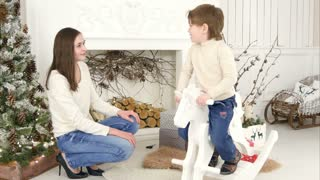 Little boy riding wooden rocking horse and talking to his mother sitting near the Christmas tree