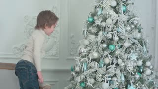 Little boy sticking his tongue out at his own reflection in the bauble on the Christmas tree