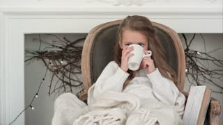 Little girl sitting in a cozy chair wrapped in a blanket drinking tea near Christmas fireplace