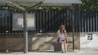 Lonely young girl waiting at bus stop in skirt, summertime