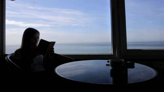 long shot of long shot silhouette of young beautiful girl sits in a cafe with panoramic views of atlantic ocean. Morning with a cup of coffe, tea, book, notepad, reading, thinkings