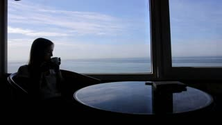 long shot of silhouette of young beautiful girl sits in a cafe with panoramic views of atlantic ocean. Morning with a cup of coffe, tea, book, drinking, thinking