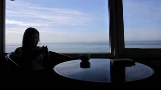 long shot of silhouette of young girl sits in a cafe with panoramic views of atlantic ocean. Morning with a cup of coffe, tea, book, notepad,  useing smart phone