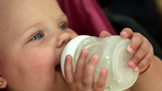 lovely little girl with blue eyes drinking milk from a bottle