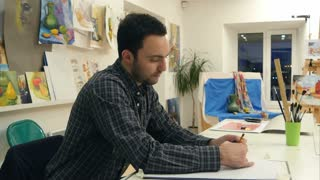 Male art student making a sketch with a pencil sitting at the desk in studio