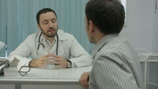 Male bearded doctor in clinicmeasure the pulse of male client.