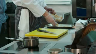 Male chef getting shrimps from container and putting them on a tray