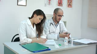 Male doctor counting money and giving it to his female partner
