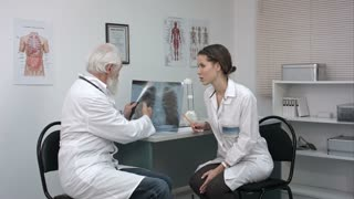 Male doctor explaining lungs x-ray to female doctor in the medical office.