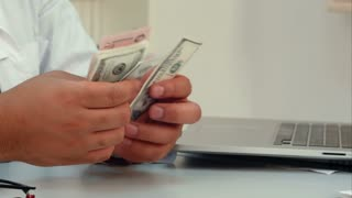 Male doctor hands counting money in the office