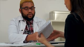 Male doctor putting money in his pocket paid by female patient for medical visit