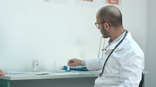 Male doctor shaking down thermometer and handing it to the patient