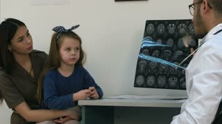 Male doctor showing brain xray results to happy and relieved woman with little girl