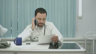 male doctor speaking on cellphone at modern hospital indoors