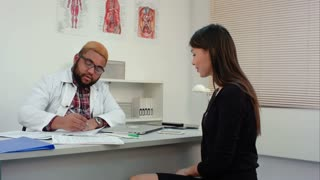Male doctor talking to female patient and filling in medical form