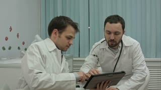 Male doctors watching on tablet pc and discussing results