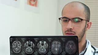 Male radiologist examining brain computed tomography