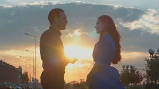 Man and woman talking during sunset. Sun shining