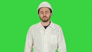 Man in the construction helmet with a raised finger on a Green Screen, Chroma Key