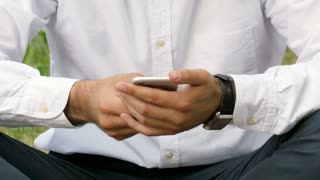 Man typing message on smart phone in the park. Focus on hands