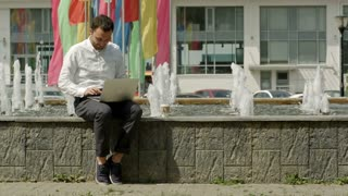 Man with laptop sitting near fountain and happy with the results of his work