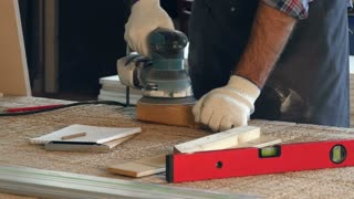 Man working with wooden planck and electric planer in workshop
