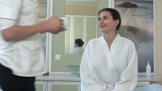 Masseuse bringing tea for her female customer in bathrobe