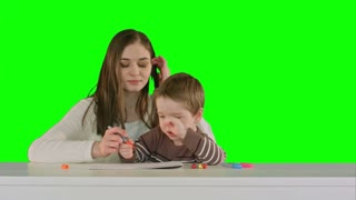 Mom and kid boy painting together on table on a Green Screen