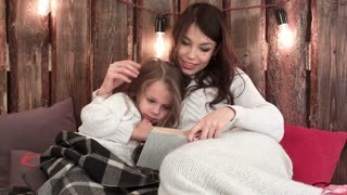 Mom with little girl reading a book and relaxing on a cozy sofa under the Christmas lights