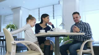 Mother, father and daughter drinking tea in cafe. Parents have a discussion after phone call