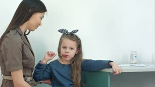 Mother talking to her little girl eating a lollipop at doctor's office