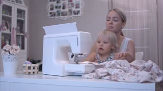 Mother teaching her baby girl how to use a sewing machine