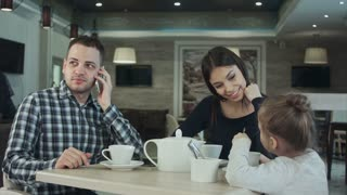 Mother trying to attract father's attention to daughter while he is busy talking to phone. Mother indignanting