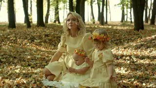 Mother with children n in sunny autumn park