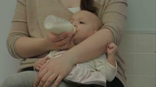 Newborn baby eating milk from bottle