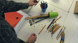 Painter arranging brushes and sharpened pencils in different jars