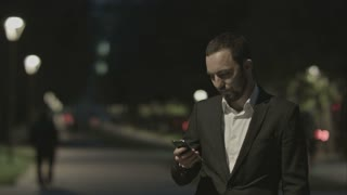 Portrait of handsome adult business man communicate by phone in good mood, while standing in the city street,business man reading messages,stylish brunette using cell phone at evening outdoors, park