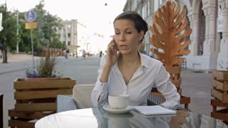 Portrait of young business woman sitting relaxed at outdoor cafe drinking coffee and calling her cell phone