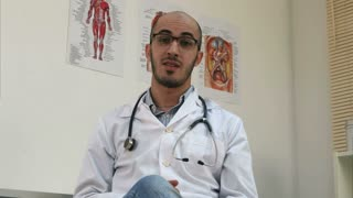 Positive male arabian doctor with stethoscope talking to the camera